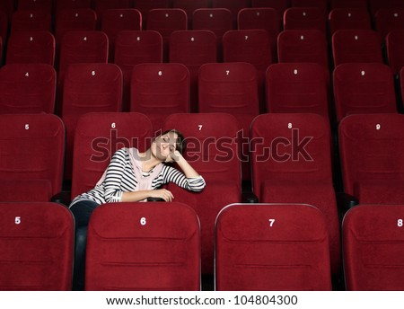 Napping woman after the movie at the cinema - stock photo