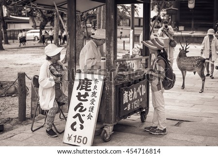 Nara, Japan - 5 Jul 2016: Sacred deer and deer food sellers at Nara park