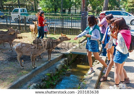 NARA, JAPAN - MARCH 28: Visitors feeding wild deer on March 28, 2014 in Nara, Japan. Nara is a major tourism destination in Japan, it is the former capital, and currently a UNESCO World Heritage Site. - stock photo