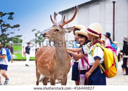 NARA,JAPAN- MAY 25, 2016:  Kids playing with wild deer in Nara on May 25, 2016. The deer in Nara have been regarded as heavenly animals, protecting the city and the country