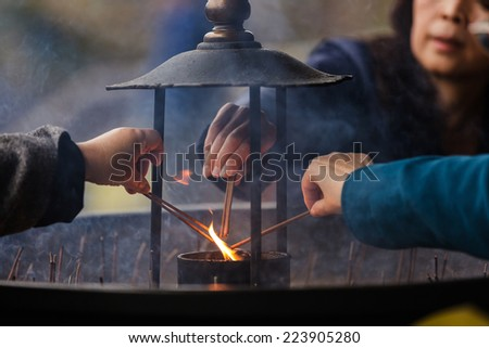 NARA,JAPAN, NOVEMBER 18, 2011: Japanese people are igniting some incense sticks for praying at the Todai-ji temple in Nara near Kyoto, Japan. Focus on the fire, shallow depth of field - stock photo