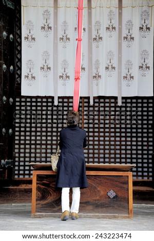 NARA, JAPAN-NOVEMBER 6, 2014; Lady praying and ringing the bell at the Eastern Golden Hall of Kofukuji temple. This is an Unesco world heritage site. November 6, 2014 Nara, Japan  - stock photo
