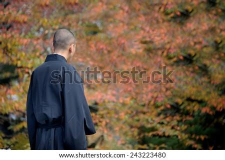 NARA, JAPAN-NOVEMBER 6, 2014; Monk at Kofukuji Temple with leafs at trees in autumn at background.This is an Unesco World Hertige site. November 6, 2014 Nara, Japan - stock photo