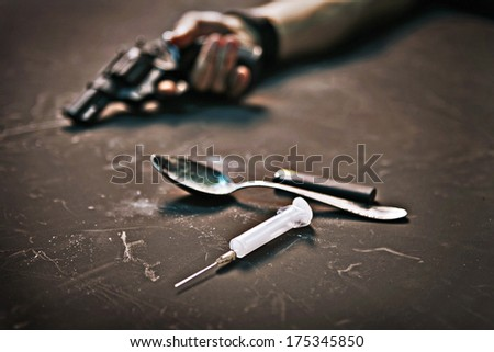 Narcomaniac / studio photography of human hand with a gun, syringe, spoon and lighter on black background  - stock photo