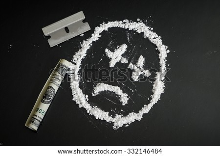 Narcotic Recreational Drugs - Sad Face in White Powder Symbolic of Addiction and Substance Abuse Issues - stock photo