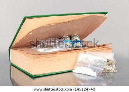 Narcotics in book-hiding place on gray background - stock photo