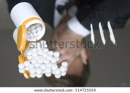 Narcotics on a mirror. Out of focus reflection of a frustrated businessman. - stock photo
