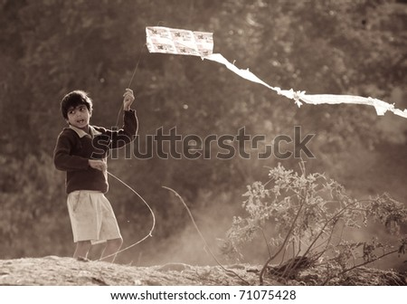 NARLAI IN INDIA - CIRCA JANUARY 2007: A young boy flies a kite circa January 2007 in Narlai, India. Kite flying is one of the main recreational pastimes for boys in this region of India. - stock photo