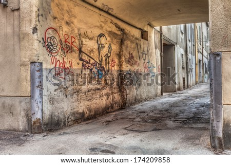 narrow alley in the old town - corner of a decadent city street and grunge wall with graffiti - draw of smoker of hashish - drug addiction, marijuana, cannabis, joint, reefer, spliff - stock photo