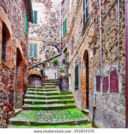 Narrow Alley with Old Buildings in Italian City of Torre Alfina - stock photo
