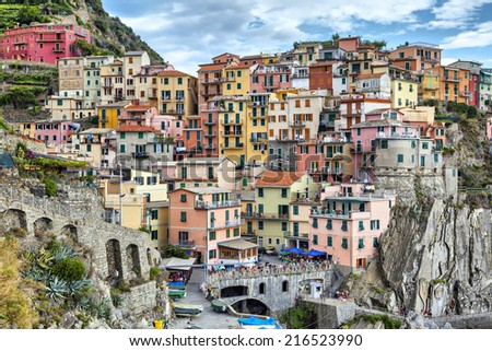 Narrow and colorful, chaotically standing houses on a cliff above the sea at summer day in Manarola, Italy - stock photo