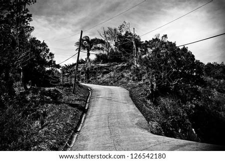 narrow and winding road high up in nature in the caribbean - stock photo