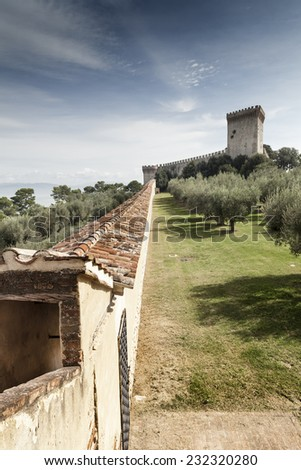 Narrow bailey road to the big fortification castle in italy, near a lake - stock photo