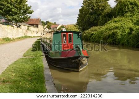 narrow boat at quay on canal, Bradford on Avon view of narrow boat  moored at quay on canal at small touristic village on river Avon  - stock photo