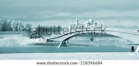 narrow bridge through ice river - stock photo