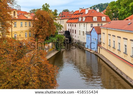 Narrow canal among colorful houses with red roofs and autumnal trees in Prague, Czech Republic.