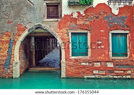 Narrow canal and facade of old red brick house in Venice, Italy. - stock photo
