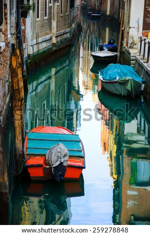 Narrow canal in Venice. Boats and reflection of colorful houses in the water. Selective focus on the  reflection. - stock photo