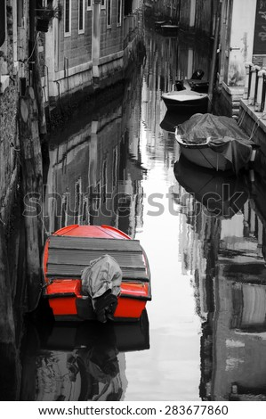 Narrow canal in Venice. Boats and reflection of houses in the water. Selective focus on the  reflection. Retro aged photo. - stock photo