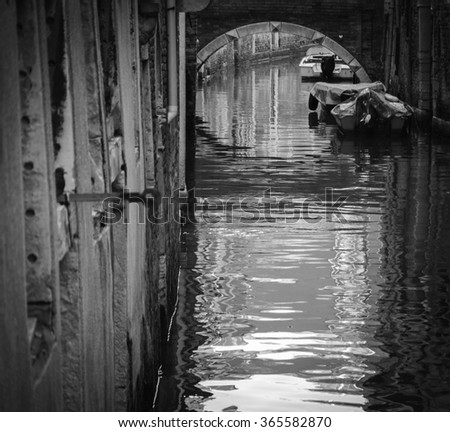 Narrow canal in Venice (Italy). Boats and reflection of houses in the water. Selective focus on the boats and reflection under the bridge. Aged photo. Black and white. - stock photo