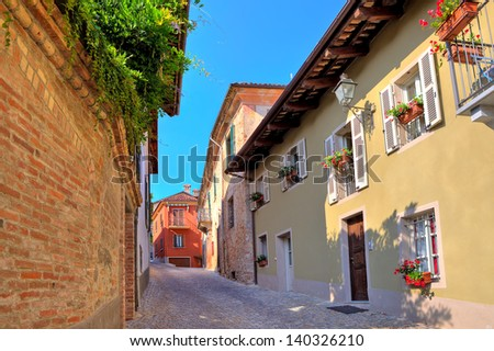 Narrow cobbled street among old brick wall and colorful houses in small town of Guarene in Piedmont, Northern Italy. - stock photo