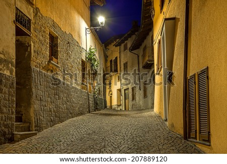 Narrow cobbled street among old houses at night in town of Barolo, Italy. - stock photo
