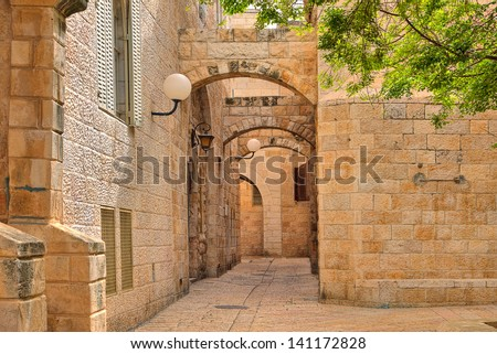 Narrow cobbled street among traditional stoned houses of jewish quarter at old historic part of jerusalem, Israel. - stock photo