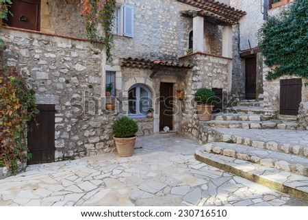 Narrow cobbled streets with flowers in the old village Gourdon, France - stock photo
