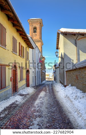 Narrow cobblestone street among house in town of Montelupo Albese in Piedmont, Italy (vertical composition). - stock photo