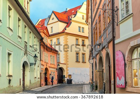 Narrow cobblestone street among typical colorful houses in Old Town of Prague, Czech Republic. - stock photo