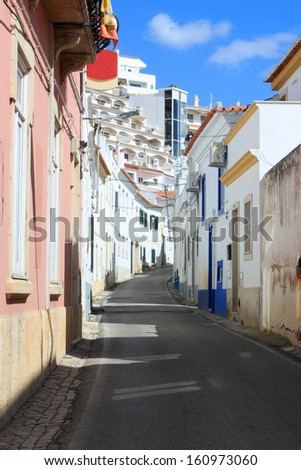 Narrow cobblestone street in old town Albufeira showing condos in the background, Algarve, Portugal - stock photo