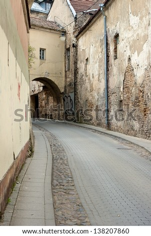 Narrow curve cobblestone road street in the old public domain European city - stock photo