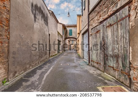 narrow dark alley in the old town - grunge aged street  - distressed alleyway in the italian city   - stock photo