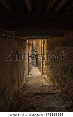 Narrow dark street of ancient medina in Fes, Morocco - stock photo