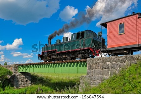 Narrow gauge steam train pulling passenger carriages. - stock photo