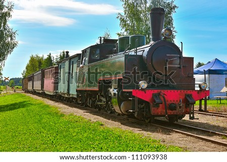 Narrow-gauge steam train pulling passenger carriages with tourists. Minkio, Finland - stock photo
