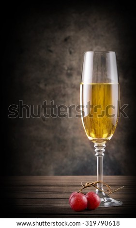 Narrow glass of white wine on wooden table - stock photo