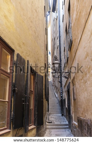 Narrow lane in European city with stairs - stock photo