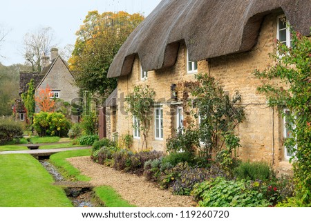 Narrow lane in vilalge of Minster Lovell in Cotswolds with stone cottages - stock photo