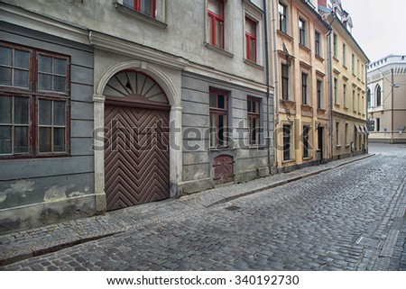 Narrow medieval street in old town of Riga city, Latvia. Walking through medieval streets of old Riga, tourists can find unique architectural ensembles and ancient houses. - stock photo