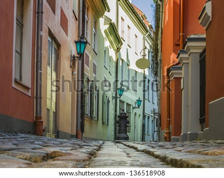 Narrow medieval street in the old Riga city, Latvia. In 2014, Riga is the European capital of culture. - stock photo