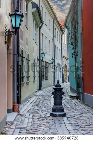 Narrow medieval street in the old Riga city. Riga is the capital and largest city of Latvia, a major cultural, historical, tourist and financial center of the Baltic region