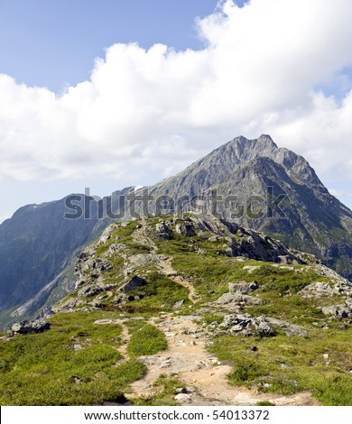 Narrow mountain path going up to a tall peak. Rauma, Norway - stock photo