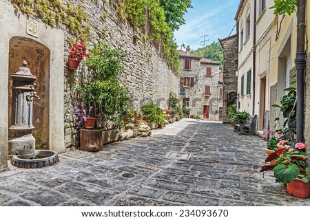 Narrow old cobbled street with flowers in Italy - stock photo