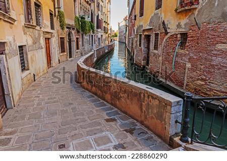 Narrow old street Canal in Venice Italy - stock photo