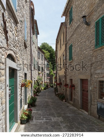 Narrow old street with flowers in Italy - stock photo