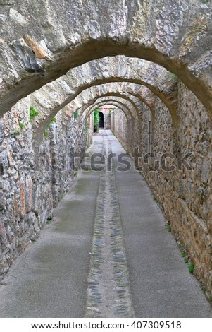 Narrow passage under stone arches from Villefranche de Conflent in the Conflent region of Catalonia, Pyrenees-Orientales department, France - stock photo