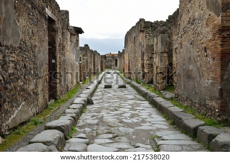 Narrow paved street is recovered in the middle of Roman ruins. Pompeii has been a popular tourist destination for over 250 years. - stock photo