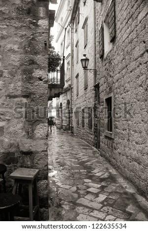 Narrow rainy european street in old and beautiful town (Italy). Monochrome image - stock photo