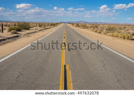 Narrow road in western desert leads into the distant mountains.